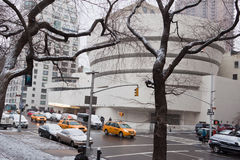 Guggenheim Museum Winter New York City. The Guggenheim Museum covered with snow, yellow cabs, leafless trees and the street traffic Stock Image