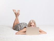 Guiño de la mujer con el ordenador portátil Foto de archivo