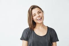 Guiño sonriente de la muchacha hermosa joven alegre mirando la cámara sobre el fondo blanco Fotografía de archivo libre de regalías