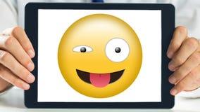 Guiño y lengua de la demostración de la tableta hacia fuera sonrientes