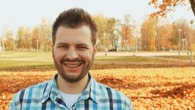 Guiños barbudos sonrientes del hombre en la cámara metrajes
