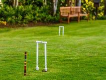 Guichet et enjeu de croquet sur la pelouse d'herbe avec le banc en bois et le jardin à l'arrière-plan Photographie stock libre de droits