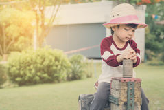 Guida asiatica del ragazzo dell'agricoltore su un camionista di legno del giocattolo Immagini Stock