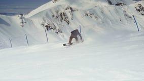 Guida attiva dello snowboarder dell'uomo sul pendio archivi video