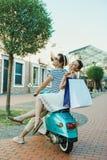 Guida casuale delle coppie sui sacchetti della spesa della tenuta e del ciclomotore all'aperto Fotografie Stock