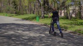Guida del bambino sul motorino di scossa in parco archivi video