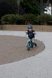 Guida del bambino sulla sua bicicletta dell'equilibrio Fotografia Stock