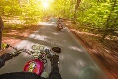 Guida del driver di motociclo nella foresta di primavera immagine stock