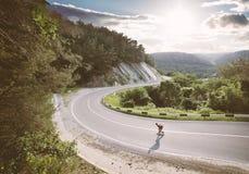 Guida del giovane su un longboard sulla strada Fotografia Stock Libera da Diritti