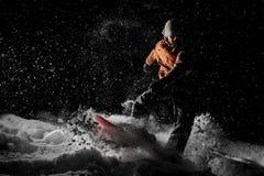 Guida del giovane sullo snowboard nella località di soggiorno di montagna nella notte fotografia stock