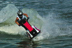 Guida del jetski nelle gocce dell'acqua Immagini Stock