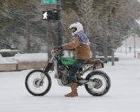 Guida del motociclo della bufera di neve in un re Street giù Immagine Stock