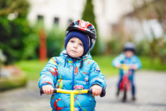 Guida del ragazzino con la sua prima bicicletta all'aperto Immagini Stock