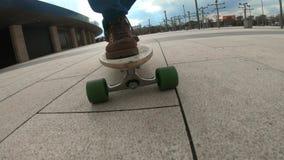 Guida del ragazzo del skateboarder del primo piano all'aperto Un giovane tipo guida un longboard nel parco Stivali d'uso del viag archivi video