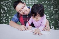Guida dell'insegnante maschio uno studente da scrivere Immagine Stock Libera da Diritti