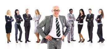 Guida dell'uomo d'affari che si leva in piedi davanti alla sua squadra Fotografie Stock Libere da Diritti