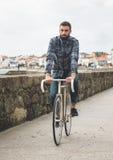 Guida dell'uomo dei pantaloni a vita bassa in una bici del fixie Immagini Stock