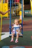 Guida della bambina sulle oscillazioni immagine stock