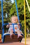 Guida della bambina sulle oscillazioni fotografia stock