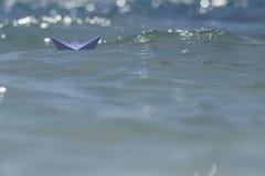 Guida della barca di origami sulle onde Fotografie Stock Libere da Diritti