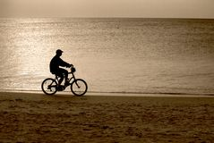 Guida della bici sulla spiaggia Fotografie Stock