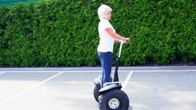 Guida della donna nei cerchi su un trasportatore personale elettrico video d archivio