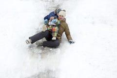 Guida della famiglia con una collina della neve Immagine Stock