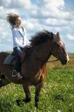 Guida della giovane donna su un cavallo marrone Fotografie Stock