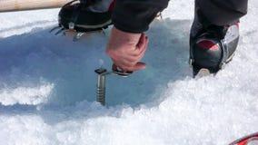 Guida della montagna che avvita una vite del ghiaccio in un ghiacciaio durante l'esercizio di allenamento Immagini Stock Libere da Diritti