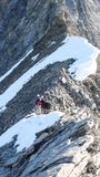 Guida della montagna che conduce due clienti maschii ad una cresta rocciosa ed in avanti ad un'alta sommità alpina Fotografia Stock Libera da Diritti