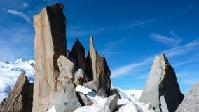 Guida della montagna e un cliente maschio su un'intestazione rocciosa della cresta verso un'alta sommità nelle alpi francesi vici Immagini Stock Libere da Diritti