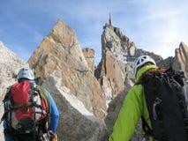 Guida della montagna e un cliente maschio su un'intestazione rocciosa della cresta verso un'alta sommità nelle alpi francesi vici Immagini Stock
