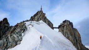 Guida della montagna e un cliente maschio su una cresta della neve che si dirige giù da un'alta sommità nelle alpi francesi vicin Fotografia Stock