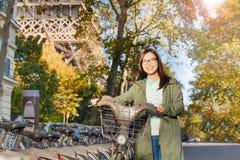 Guida della ragazza attraverso Parigi con la bici locativa Fotografia Stock Libera da Diritti