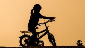 Guida della ragazza nel sole di pomeriggio Fotografia Stock