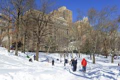Guida della slitta dei bambini nella neve Immagini Stock