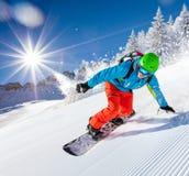 Guida dello snowboarder dell'uomo sul pendio fotografia stock libera da diritti