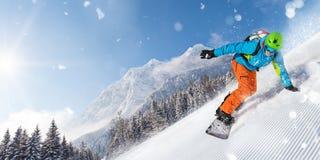 Guida dello snowboarder dell'uomo sul pendio immagine stock