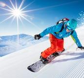 Guida dello snowboarder dell'uomo sul pendio immagini stock libere da diritti
