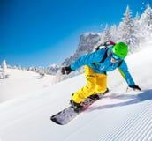 Guida dello snowboarder dell'uomo sul pendio fotografie stock libere da diritti