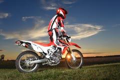 Guida di Byker di motocross durante il tramonto Fotografie Stock