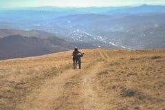 Guida di scena della montagna con un mountain bike fornito delle borse di viaggio fotografia stock