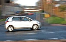 Guida di veicoli bianca vaga nella città. Immagini Stock