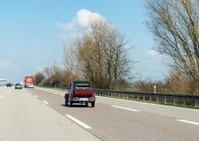 Guida di veicoli d'annata di Citroen 2CV sulla strada principale Fotografia Stock