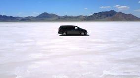 Guida di veicoli d'argento seguente obliqua del furgoncino di volo del fuco in mezzo al deserto strabiliante del lago di sale del video d archivio