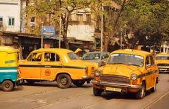 Guida di veicoli gialla del taxi sulla strada affollata della città indiana Fotografia Stock Libera da Diritti