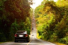 Guida di veicoli lungo la strada che aumenta al cielo da parte a parte Fotografia Stock