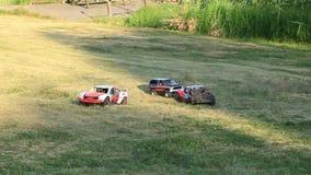 Guida di veicoli parecchi controllata radiofonica del giocattolo sul prato inglese il giorno di estate Incidente stradale Due aut video d archivio