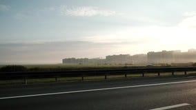 Guida di veicoli su ad alta velocità fuori del centro della città Vista su nuovi infrastruttura e costruzioni o distretti svilupp video d archivio