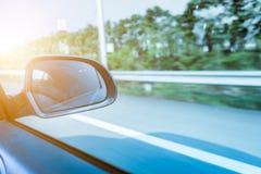 Guida di veicoli sul cielo della strada principale, specchietto retrovisore laterale immagini stock libere da diritti